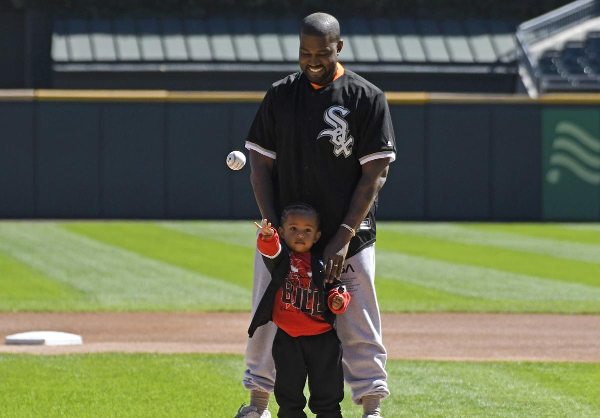 Kanye West and his son Saint throw out a ceremonial first pitch before the game between the Chicago White Sox and the Chicago Cubs on September 23, 2018 at Guaranteed Rate Field in Chicago, Illinois
