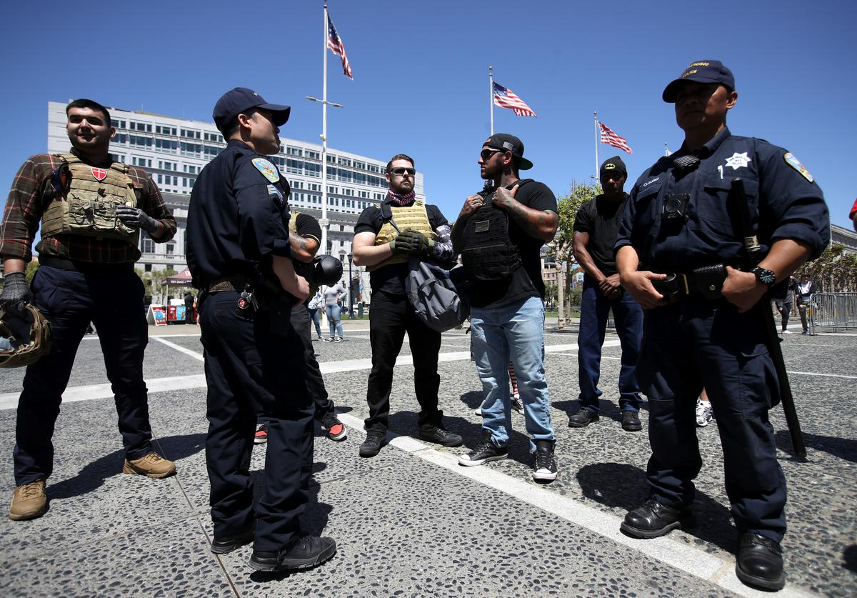 San Francisco police officers stand between a group of far right activists wearing body armor and anti-fascist protesters during a freedom of speech rally