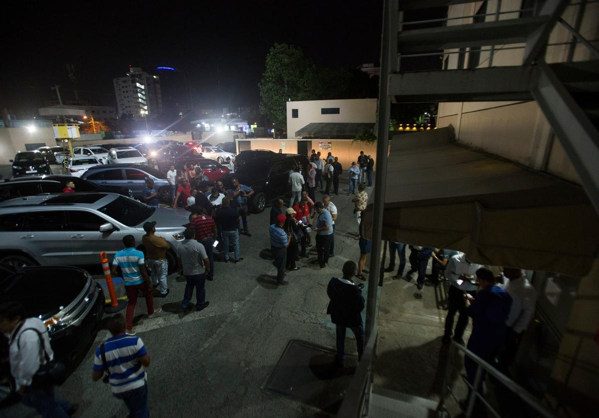 Journalists gather outside the clinic where Dominican television presenter Joel Lopez and former Boston Red Sox slugger David Ortiz