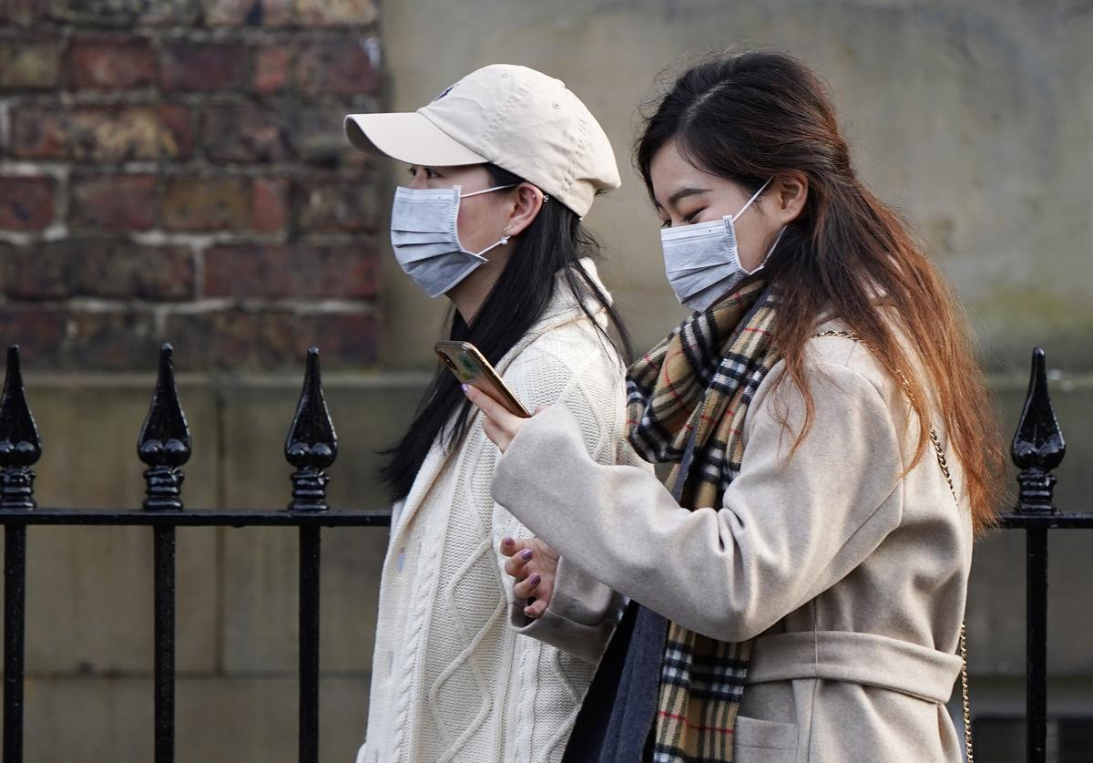 Two women wearing face masks walk through the city centre near to the Royal Victoria Infirmary where two patients who have tested positive for the Wuhan coronavirus are being treated by specialist medical workers on January 31, 2020 in Newcastle upon Tyne, England. Two people in the same family have been diagnosed with the Coronavirus in the UK, which has killed at least 213 people in China. (