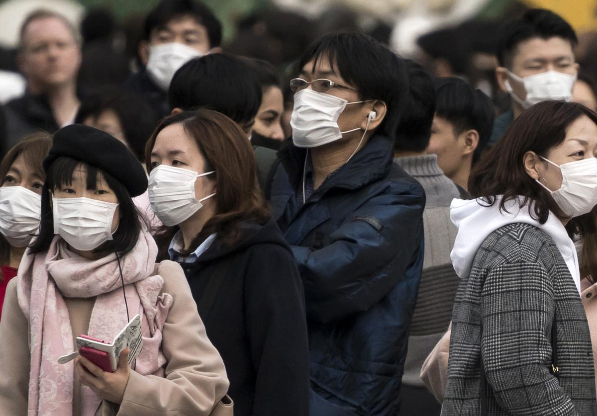 People wearing masks wait to cross a road in the Shibuya district (Feb. 2020)