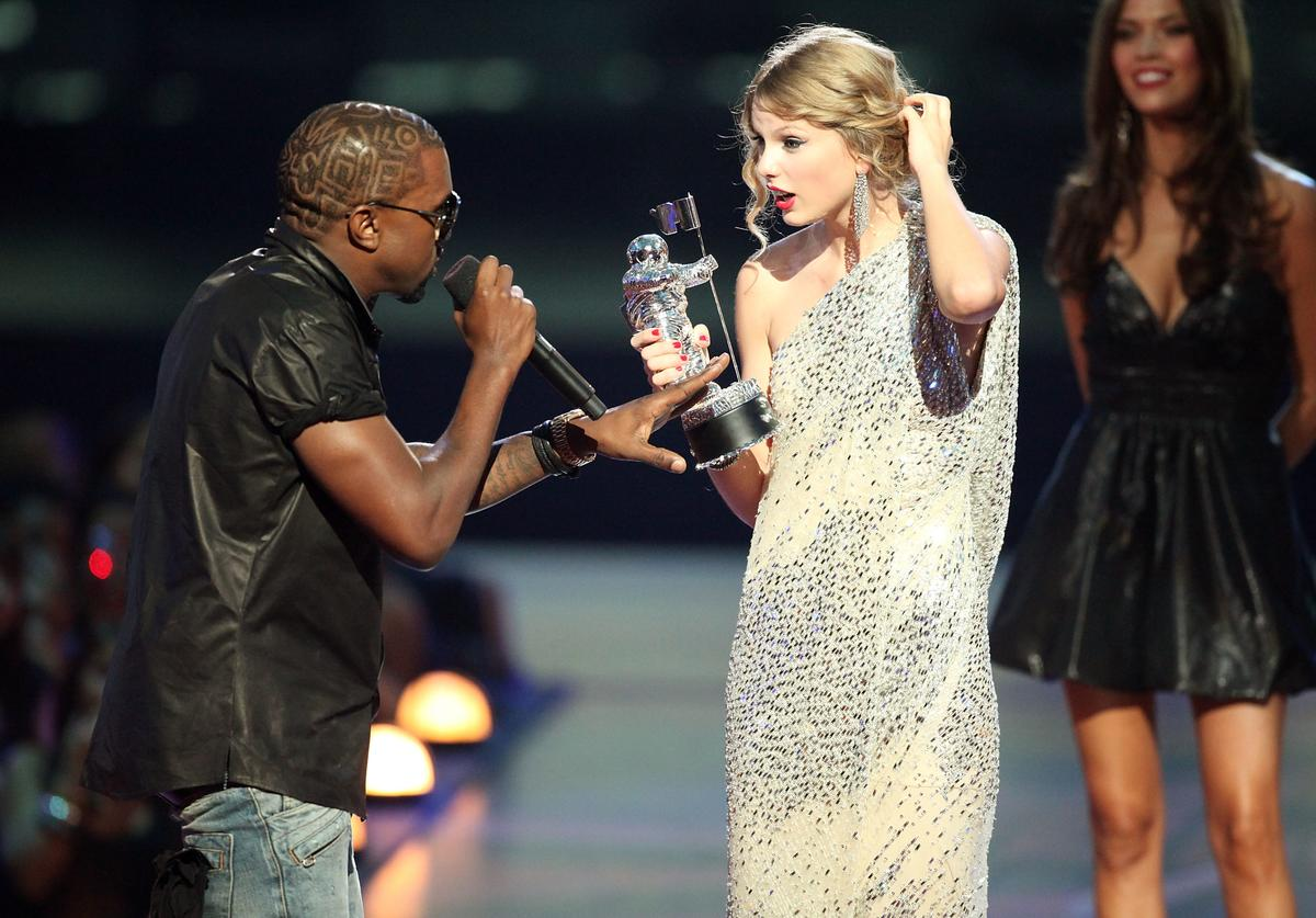 Kanye West (L) jumps onstage after Taylor Swift (C) won the 'Best Female Video' award during the 2009 MTV Video Music Awards at Radio City Music Hall on September 13, 2009 in New York City