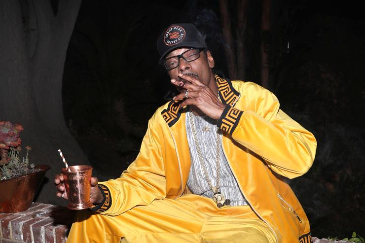 Snoop Dogg smoking a joint with a drink in the other hand