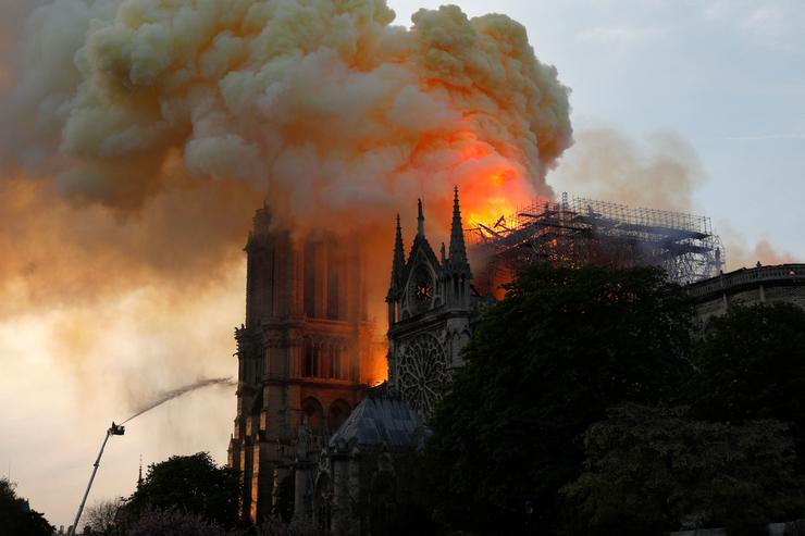 A firefighter uses a hose to douse flames and smoke billowing from the roof at Notre-Dame Cathedral in Paris on April 15, 2019