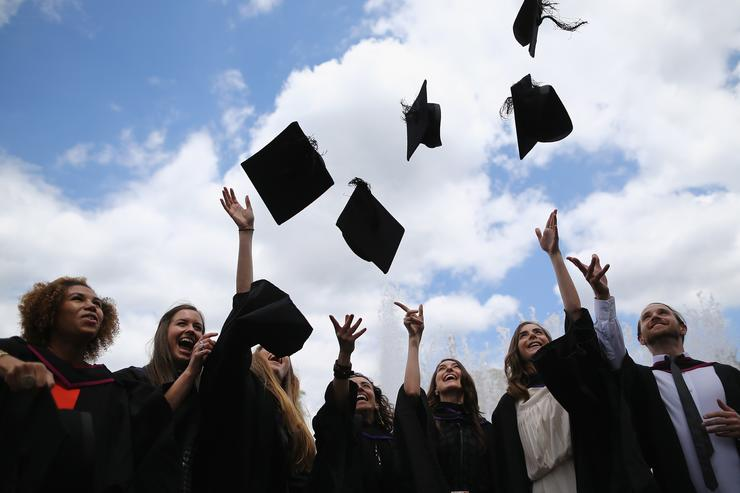 Students throw their caps in the air ahead of their graduation ceremony at the Royal Festival Hall on July 15, 2014 in London, England. Students of the London College of Fashion, Management and Science and Media and Communication attended their graduation ceremony at the Royal Festival Hall today.