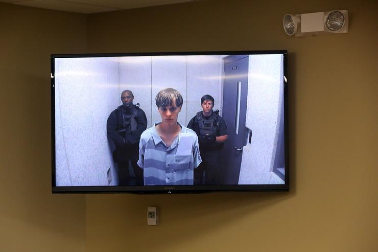 In this image from the video uplink from the detention center to the courtroom, Dylann Roof appears at Centralized Bond Hearing Court June 19, 2015 in North Charleston, South Carolina. Roof is charged with nine counts of murder and firearms charges in the shooting deaths at Emanuel African Methodist Episcopal Church in Charleston, South Carolina on June 17.