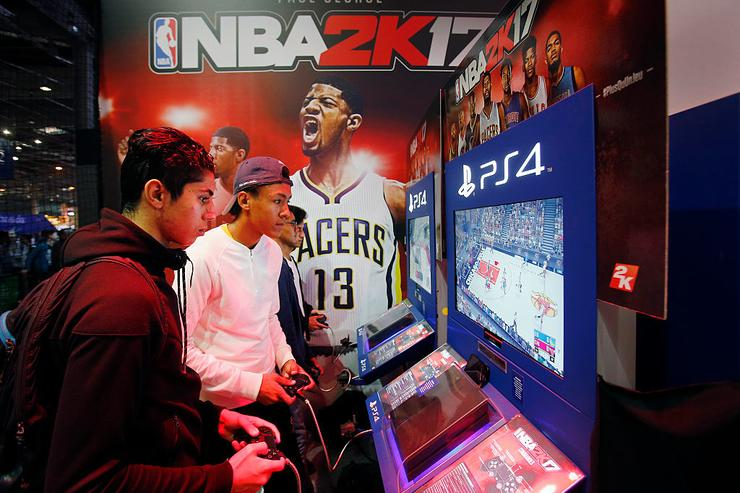 Gamers play the video game 'NBA 2K 17' developed by Visual Concepts and published 2K Sports on Sony PlayStation game consoles PS4 during the 'Paris Games Week' on October 28, 2016 in Paris, France. 'Paris Games Week' is an international trade fair for video games to be held from October 27 to October 31, 2016.