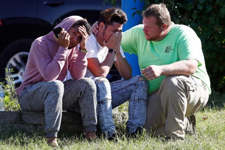 People sit distraught after a shooting in Maryland