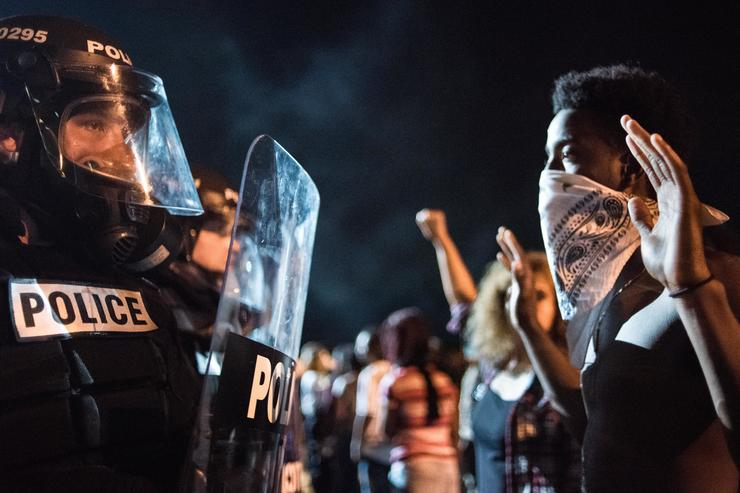 Police officers face off with protesters on the I-85 (Interstate 85) during protests in the early hours of September 21, 2016 in Charlotte, North Carolina. The protests began last night, following the fatal shooting of 43-year-old Keith Lamont Scott by a police officer at an apartment complex near UNC Charlotte