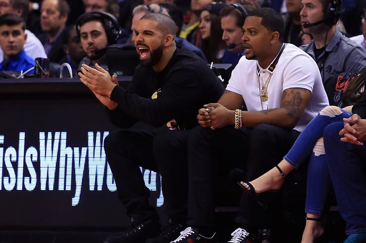 Drake cheers from his courtside seat during the first half of an NBA game between the Golden State Warriors and the Toronto Raptors at Air Canada Centre on November 16, 2016