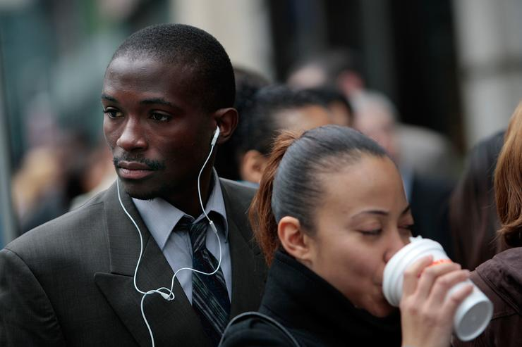 A job seeker listens to earphones as another drinks a hot beverage while waiting to enter a job fair in midtown Manhattan April 14, 2009 in New York City. Job hopefuls began lining up at 7 am for the 11 am job fair, searching for employment in a city that has shed tens of thousands of jobs in the last year