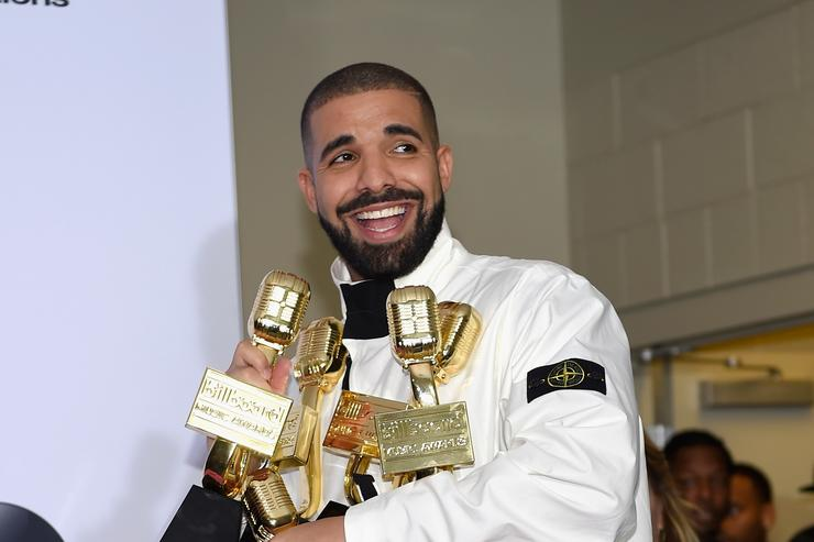 Drake smiling with a bunch of awards