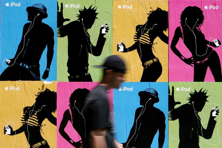 A pedestrian passes a wall covered with Apple iPod advertisements July 14, 2005 in San Francisco, California. Shares of Apple Computer surged Thursday after the company reported its best quarterly profit ever. Apple?s net income rose to $320 million, or 37 cents per share, up from the $61 million and 8 cents per share the company reported in the same quarter last year