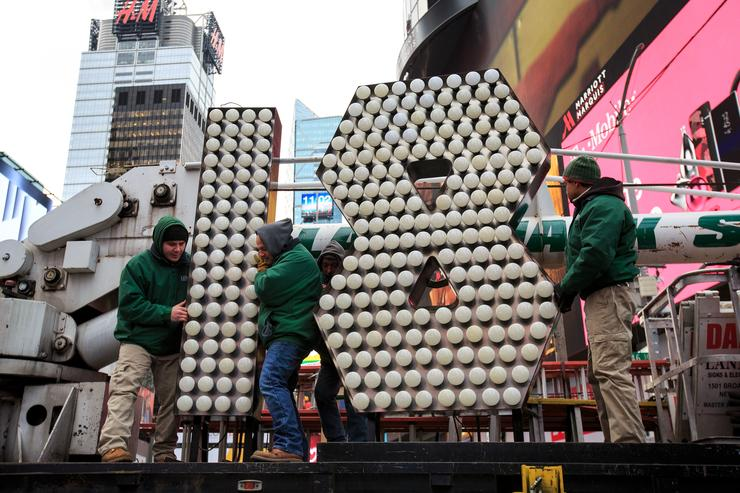 Workers unload the numerals 1 and 8 as they arrive in Times Square ahead of the New Year's Eve celebration, December 13, 2017 in New York City. The '18' numerals will be part of the '2018' sign that will light up light up above Times Square at midnight on December 31 to ring in the new year