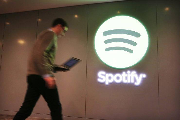 A Spotify employee walks out of a news conference where Spotify CEO Daniel Ek announced that the online streaming music service will expand to 20 new markets around the world and that it has worked out a deal with Led Zeppelin, which had so far refused to license its catalog for streaming on the service on December 11, 2013 in New York City. The new markets will include a number of countries in Europe and South and Central America and the music service will now allow free streaming to mobile devices