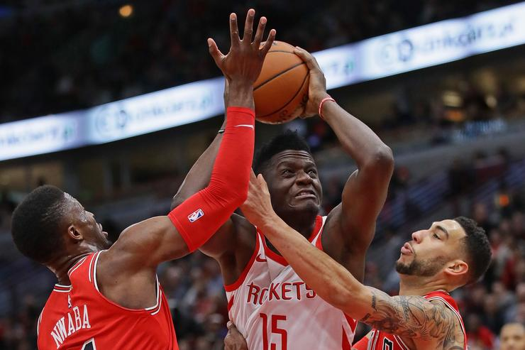 Clint Capela #15 of the Houston Rockets drives between David Nwaba #11 and Denzel Valentine #45 of the Chicago Bulls at the United Center on January 8, 2018 in Chicago, Illinois