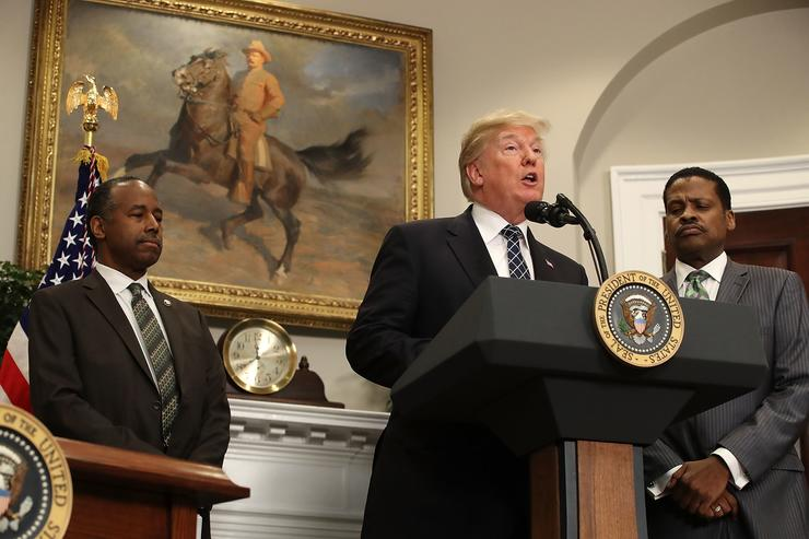 President Donald Trump speaks while flanked by HUD Secretary Dr. Ben Carson (L) and Isaac Newton Farris, Jr., before signing a proclamation to honor Martin Luther King, Jr. day, in the Roosevelt Room at the White House, on January 12, 2018 in Washington, DC. Monday January 16 is a federal holiday to honor Dr. King and his legacy